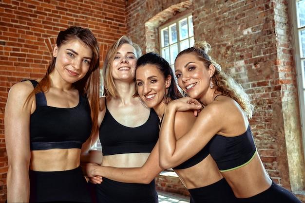 Grupa pięknych dziewczyn sportowych po treningu dobrze się bawi, łatwo się męczy, gratulacje dla siebie z doskonałymi wynikami i dobrym treningiem. uśmiecha się i pozuje do kamery.