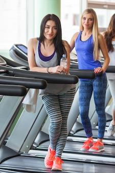 Grupa pięknych dziewczyn w dobrej formie biegających na bieżniach. ładne kobiety trenuje w gym. dziewczyna uśmiecha się do kamery