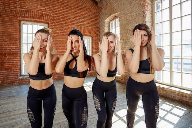 Grupa pięknych dziewczyn z rękami ukrywającymi twarze.