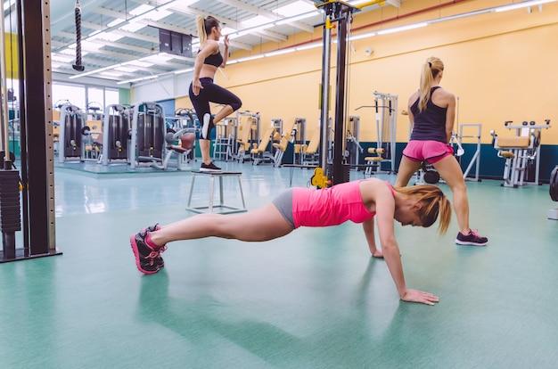 Grupa pięknych kobiet ciężko trenujących w torze crossfitowym w centrum fitness