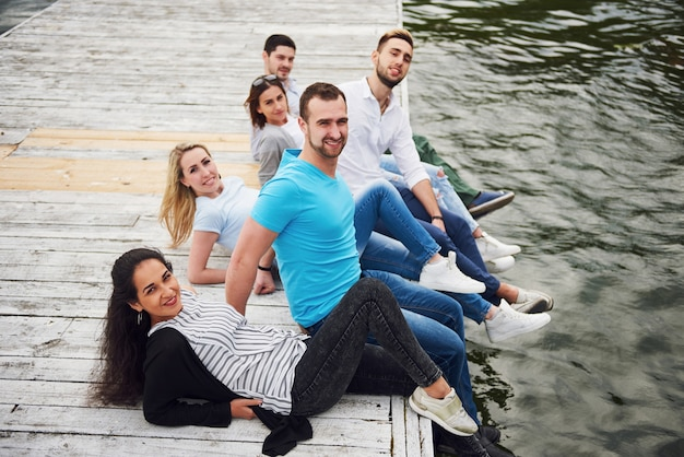 Grupa pięknych młodych ludzi na molo, satysfakcja przyjaciół stwarza życie emocjonalne.