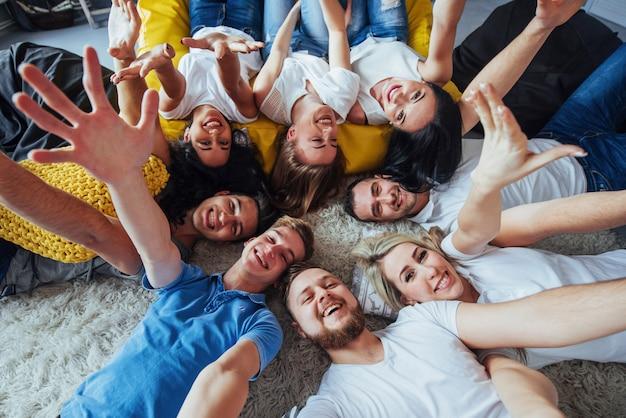 Grupa pięknych młodych ludzi robi selfie leżących na podłodze, najlepsi przyjaciele dziewczyny i chłopcy wspólnie bawią się, stwarzając emocjonalny styl życia