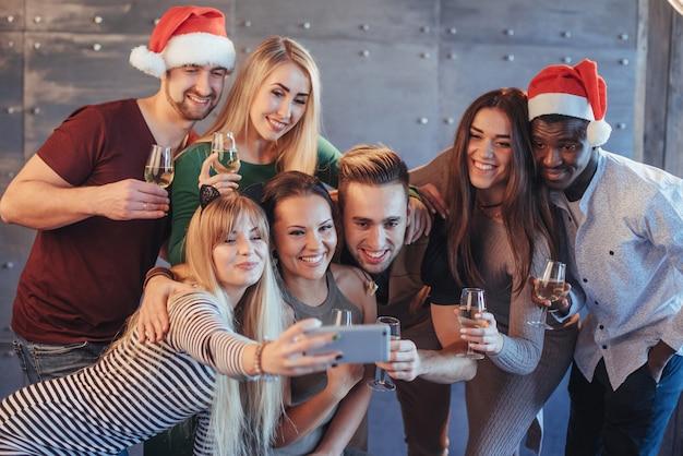 Grupa pięknych młodych ludzi robi selfie na imprezie noworocznej, najlepsi przyjaciele dziewczyny i chłopcy bawią się razem, stwarzając emocjonalny styl życia. kapelusze mikołaje i kieliszki do szampana w rękach