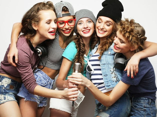 Grupa pięknych stylowych hipsterek śpiewających karaoke