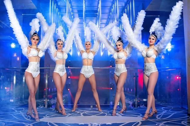 Grupa pięknych tancerek w białych strojach karnawałowych