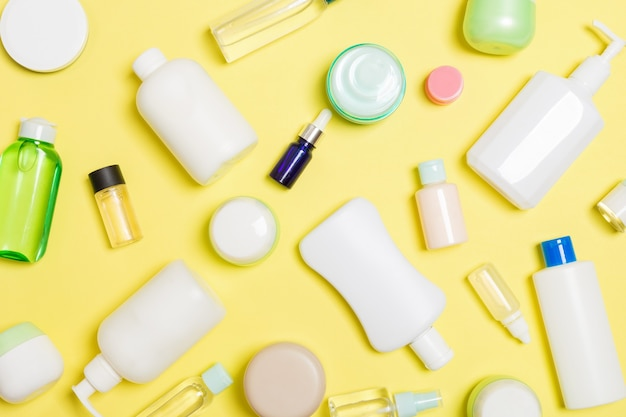 Grupa plastikowej butelki do pielęgnacji ciała płaski świecki skład z produktów kosmetycznych na żółtym tle pustej przestrzeni dla ciebie projekt. zestaw białych pojemników kosmetycznych, widok z góry z miejsca na kopię.