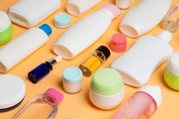 Grupa plastikowych butelek do pielęgnacji ciała płaski świeckich skład z produktów kosmetycznych na kolorowym tle pustej przestrzeni dla ciebie projekt. zestaw białych pojemników kosmetycznych, widok z góry z miejsca na kopię.
