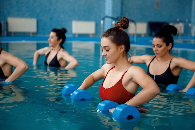 Grupa pływaczek, aqua aerobik, trening z hantlami w basenie