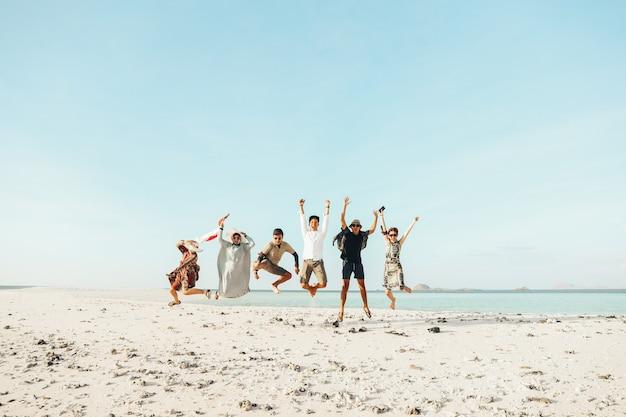 Grupa podekscytowanych azjatów cieszących się wakacjami ze wspólnymi skokami na plaży