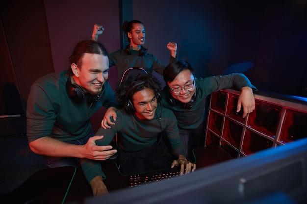 Grupa podekscytowanych graczy cieszy się ze zwycięstwa w grze komputerowej, patrząc na monitor komputera i uśmiechając się podczas gry