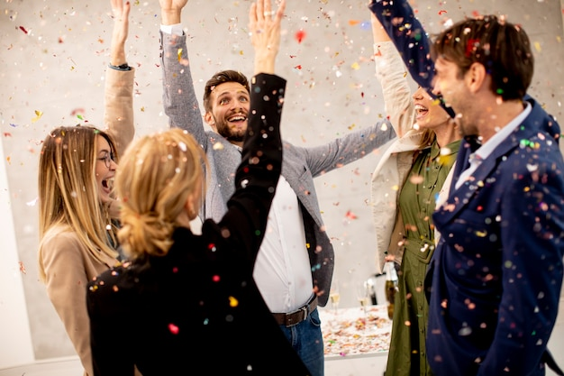 Grupa podekscytowanych ludzi biznesu obchodzi i toast z konfetti spada w biurze