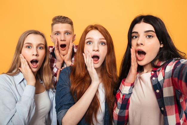 Grupa podekscytowanych szkolnych przyjaciół biorących selfie