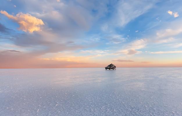Grupa podróżna stoi na solnisku uyuni o zachodzie słońca w boliwii w ameryce południowej