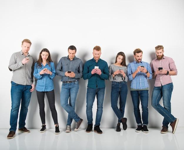 Grupa połączonych chłopców i dziewcząt wysyła wiadomości za pomocą swoich smartfonów. pojęcie internetu i sieci społecznościowej