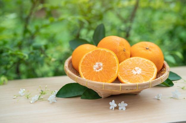 Grupa pomarańczy w koszu i na drewnianym stole.