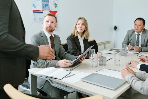 Grupa poważnych brokerów odzieży wizytowej, przyglądająca się i słuchająca mówcy stojącego przed nimi i rozmawiających o kwestiach finansowych