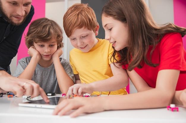 Grupa pozytywnie uważnych dzieci z nauczycielem gromadzących się wokół stołu z tabletem i elektronicznymi detalami oraz omawiających projekt badawczy podczas lekcji robotyki w szkole