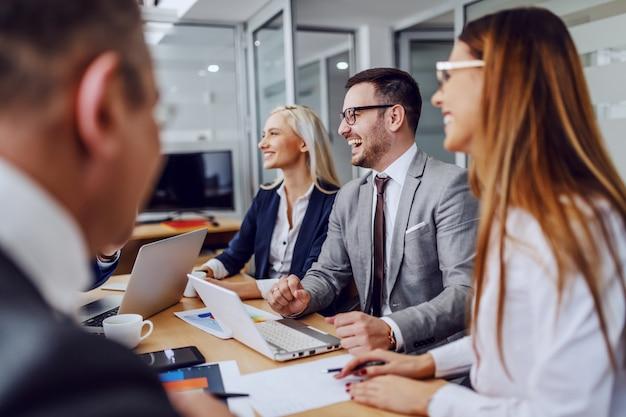 Grupa pozytywnych ludzi biznesu siedzi w sali konferencyjnej i burzy mózgów.