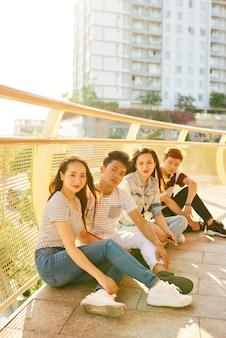 Grupa pozytywnych młodych ludzi siedzących na mostku w ciepłych promieniach jesiennego słońca