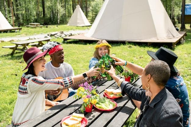 Grupa pozytywnych wieloetnicznych przyjaciół siedzi przy stole z przekąskami i razem pije piwo na kempingu