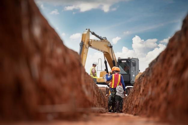 Grupa pracownik i inżynier budowy nosić bezpieczeństwo jednolite wykopywanie odwodnienie wody