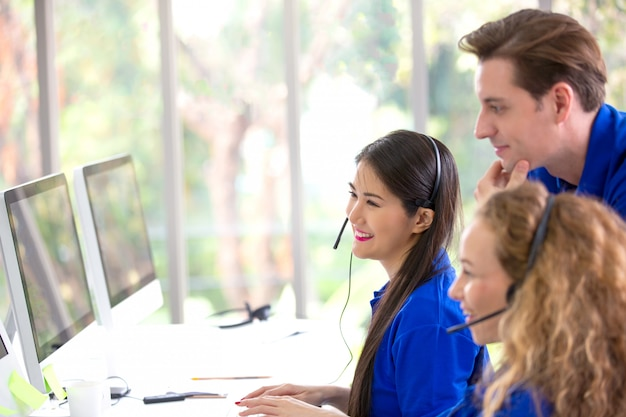 Grupa pracowników call center biznesowych pracujących przed monitorem