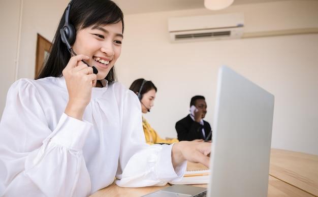 Grupa pracowników call center rozmawia i świadczy usługi klientom za pośrednictwem słuchawek i kabla mikrofonowego. specjaliści z umiejętnościami mówienia, pamięci i nagrywania informacji. relaksujący czas