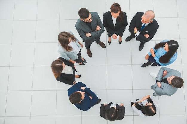 Grupa pracowników korporacji stojących w kręgu