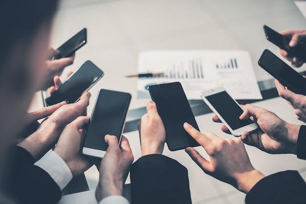 Grupa pracowników korzystających ze swoich smartfonów
