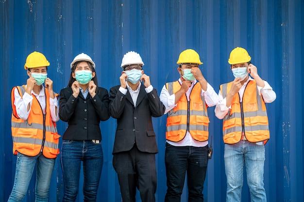Grupa pracowników na placu budowy nosi ochronne maski na twarz i kaski ochronne