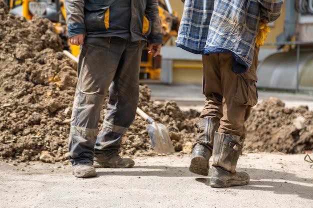 Grupa pracowników stoi w pobliżu odkrywki w brudnych ubraniach