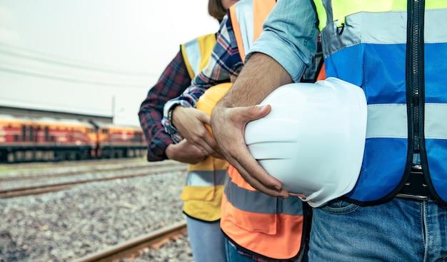 Grupa pracowników trzymających kask i inżynierów odpoczywała na torach po ciężkiej pracy