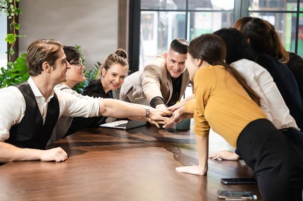 Grupa pracowników tworzy stos rąk na pulpicie z kierownikiem prowadzącym w celu osiągnięcia sukcesu w projekcie