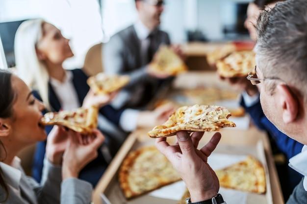 Grupa pracowników umysłowych podczas przerwy obiadowej, głodni i cieszący się pizzą.