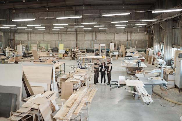 Grupa pracowników współczesnej fabryki omawia materiały do produkcji mebli, podczas gdy kierownik sprzedaży wskazuje na nich na spotkaniu