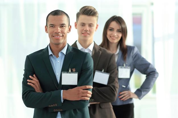 Grupa pracowników z pustymi identyfikatorami, stojących jeden za drugim w biurze
