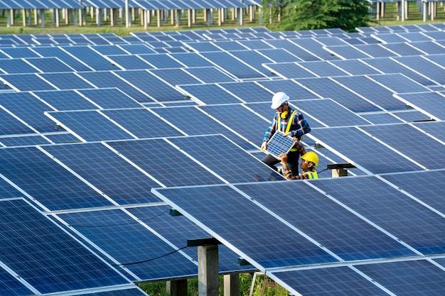 Grupa pracuje nad sprawdzaniem i konserwacją przy użyciu baterii słonecznych w pobliżu paneli słonecznych w słoneczny dzień w elektrowni słonecznej.