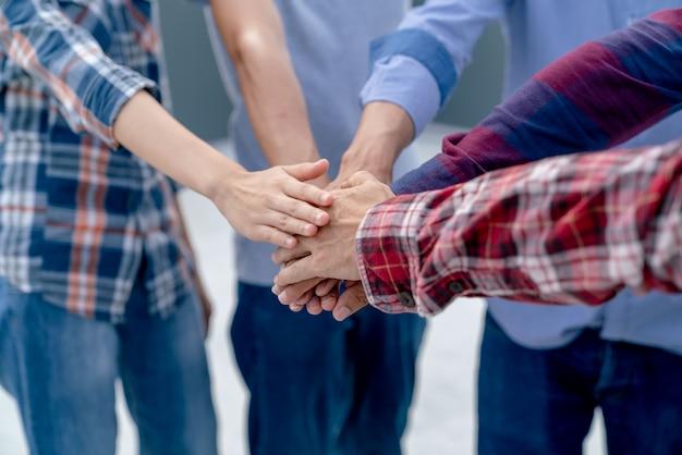 Grupa pracy zespołowej oficera jest szczęśliwa i łączy ręce, aby świętować sukces w zakończeniu planowania pracy