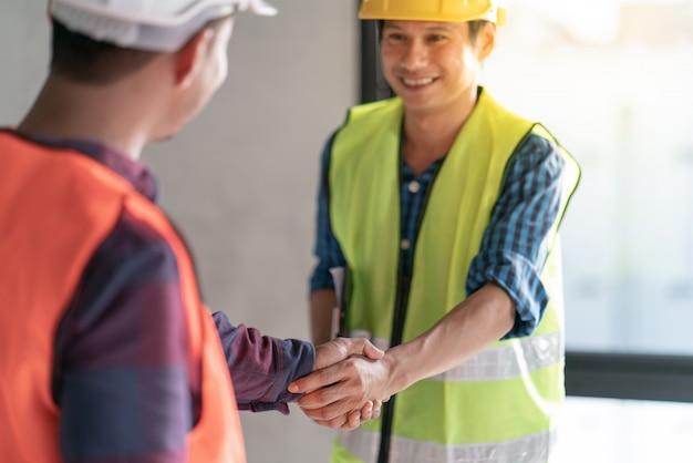 Grupa pracy zespołowej oficera jest szczęśliwa i podaje uścisk dłoni, aby świętować sukces w zakończeniu planowania pracy w projekcie budowy domu