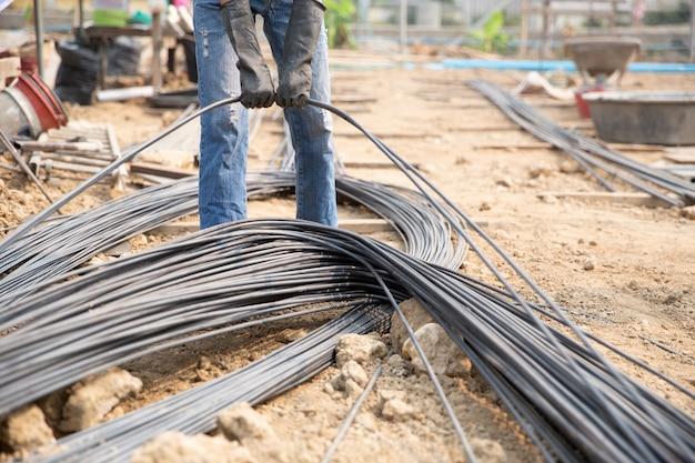 Grupa prętów stalowych napiętych łańcuchowo i podnoszących się na placu budowy