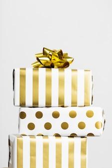 Grupa prezentów w białym i złotym papierze na szarej powierzchni