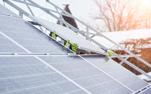 Grupa profesjonalistów instalujących fotowoltaiczne panele słoneczne na dachu nowoczesnego domu w czasie śnieżnej zimy. alternatywne źródło energii odnawialna energia elektryczna słońce ekologiczna produkcja elektrownia