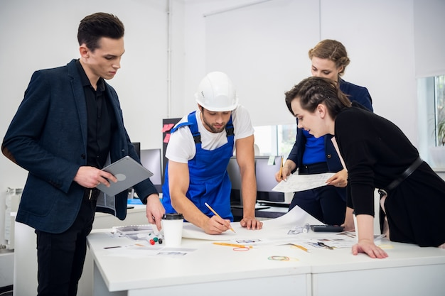 Grupa profesjonalnych inżynierów uważnie analizujących projekt