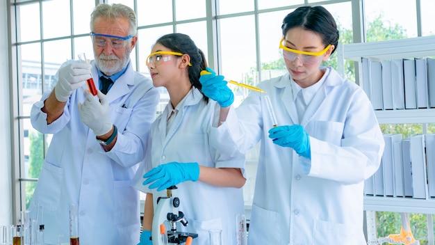 Grupa profesorów naukowców z białą suknią przygotowuje testujący płyn chemiczny z wyposażeniem naukowym na biurku. z koncentracją twarzy.
