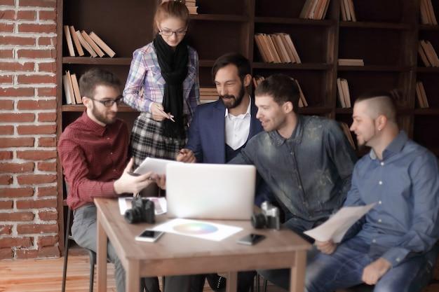 Grupa projektantów i fotografów używa do pracy komputera typu tablet.zdjęcie z miejscem na kopię