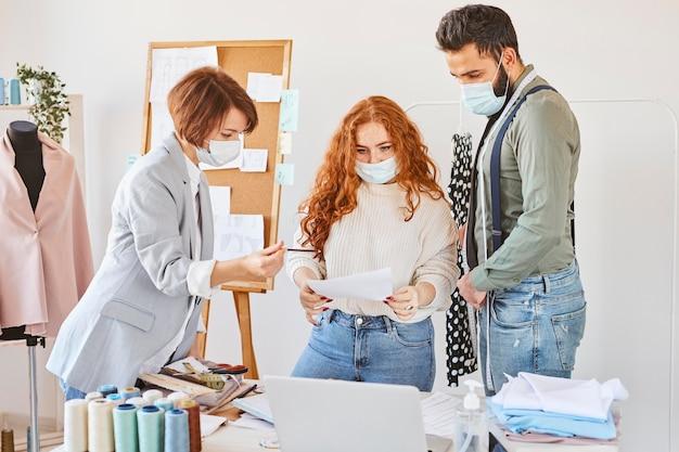 Grupa projektantów mody pracujących w atelier z maskami medycznymi i papierem