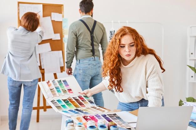 Grupa projektantów mody pracujących w atelier z paletą kolorów i tablicą pomysłów