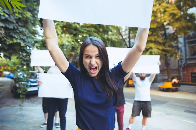 Grupa protestujących młodych ludzi na zewnątrz