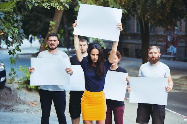 Grupa protestujących młodych ludzi w plenerze demonstranci demonstranci demokracja