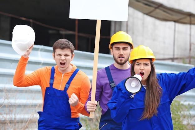 Grupa protestujących młodych pracowników z transparentami